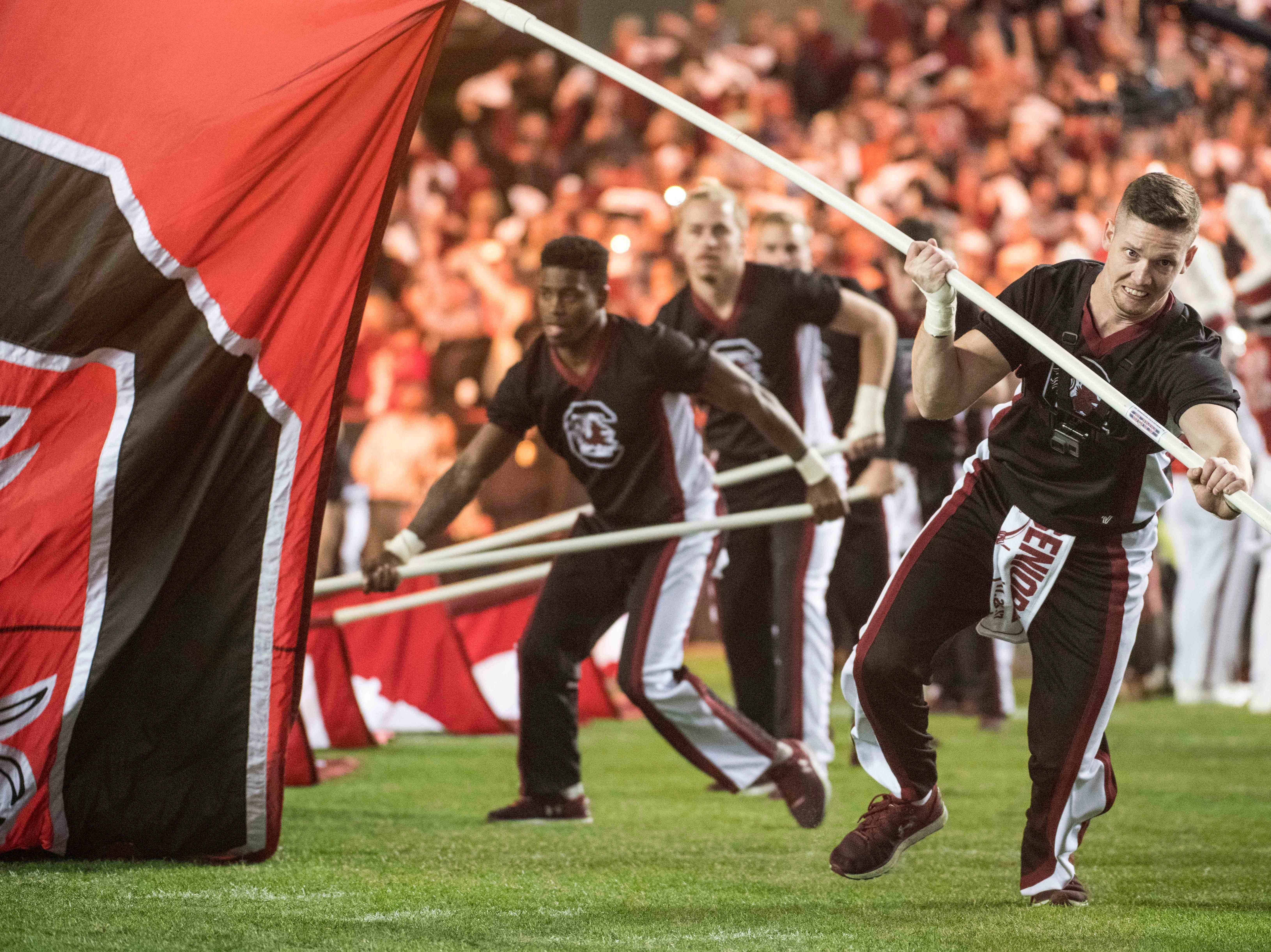 South Carolina cheerleaders lead players onto the field before an NCAA college football game against Clemson on Saturday, Nov. 25, 2017, in Columbia, S.C. Clemson defeated South Carolina 34-10. (AP Photo/Sean Rayford)