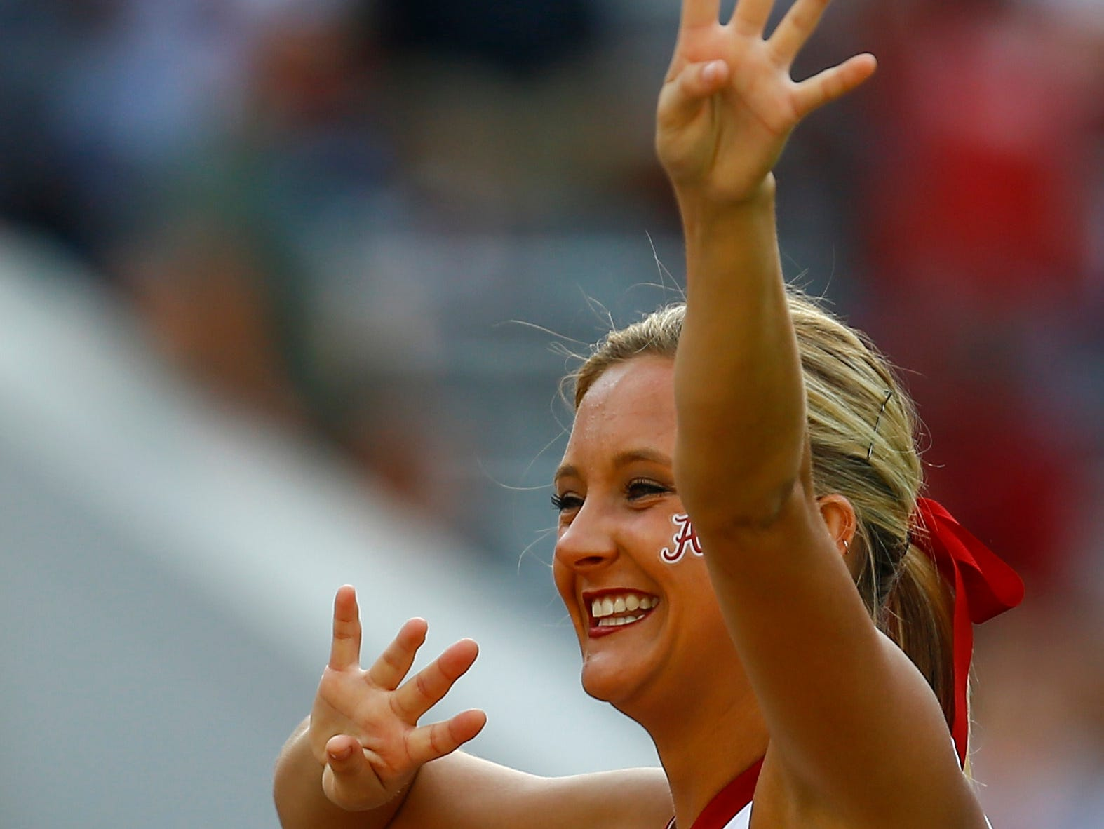 An Alabama cheerleader signals for the fourth quarter during the second half of an NCAA college football game between Alabama and Arkansas State, Saturday, Sept. 8, 2018, in Tuscaloosa, Ala. (AP Photo/Butch Dill)