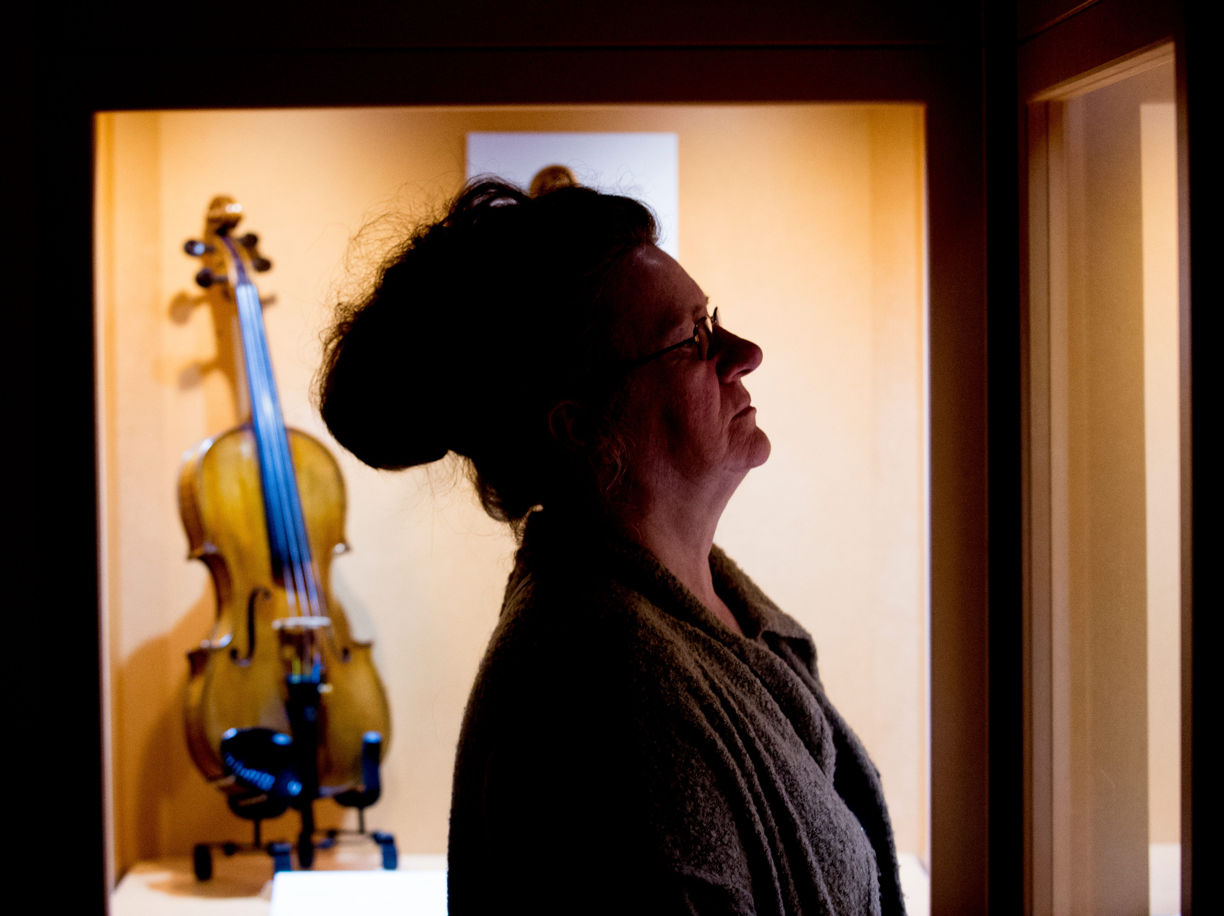 Donna Burton, of Cleveland, Ohio, looks at the Violins of Hope exhibit at the University of Tennessee Downtown Gallery, 106 S. Gay St., in Knoxville, Tennessee on Friday, January 4, 2019. The exhibit, from Israel, features 38 violins that were played by Jewish musicians during the Holocaust. The display runs from Jan. 4-27.