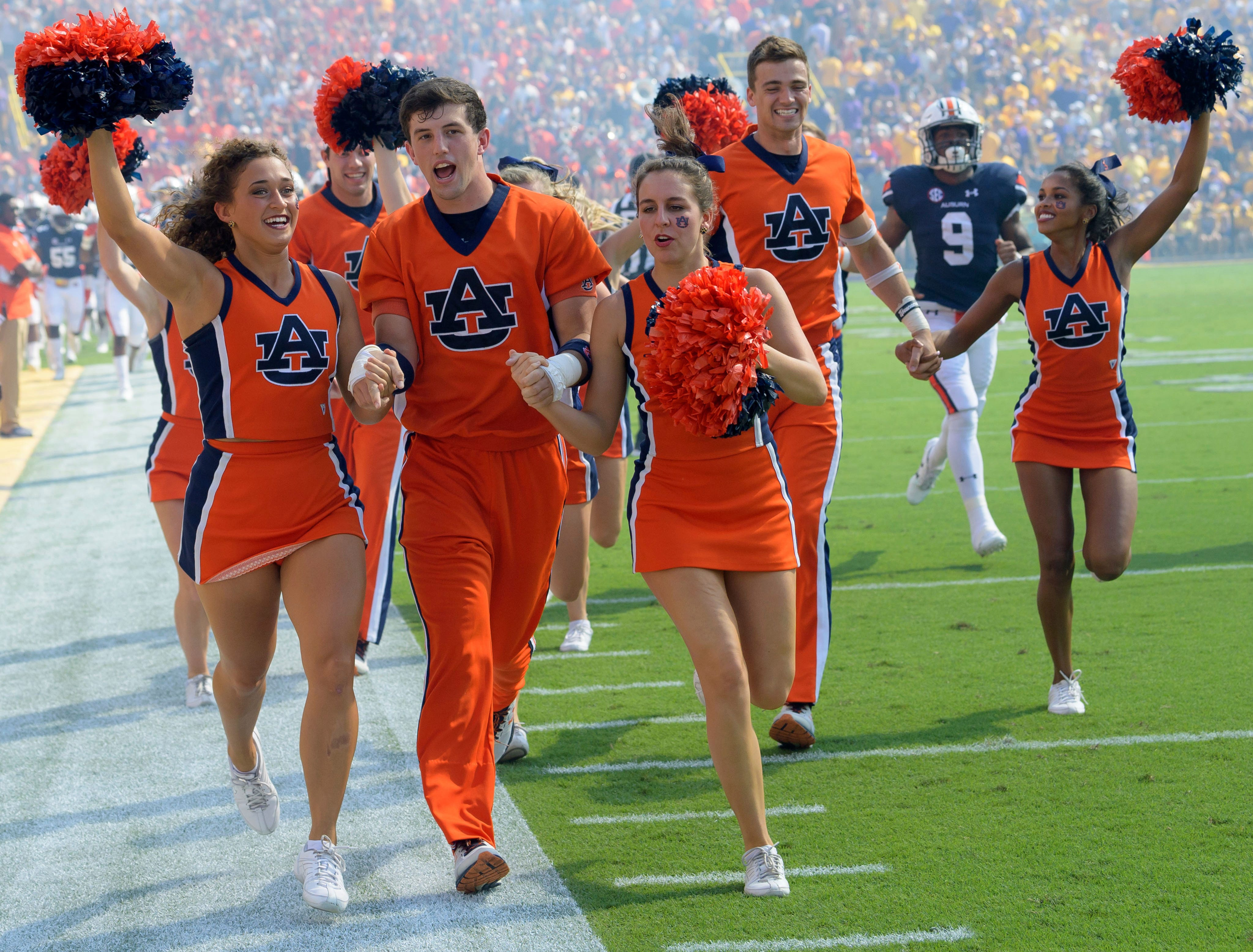 Auburn cheerleaders run onto the field before an NCAA college football game against LSU in Baton Rouge, La., Saturday, Oct. 14, 2017. (AP Photo/Matthew Hinton)