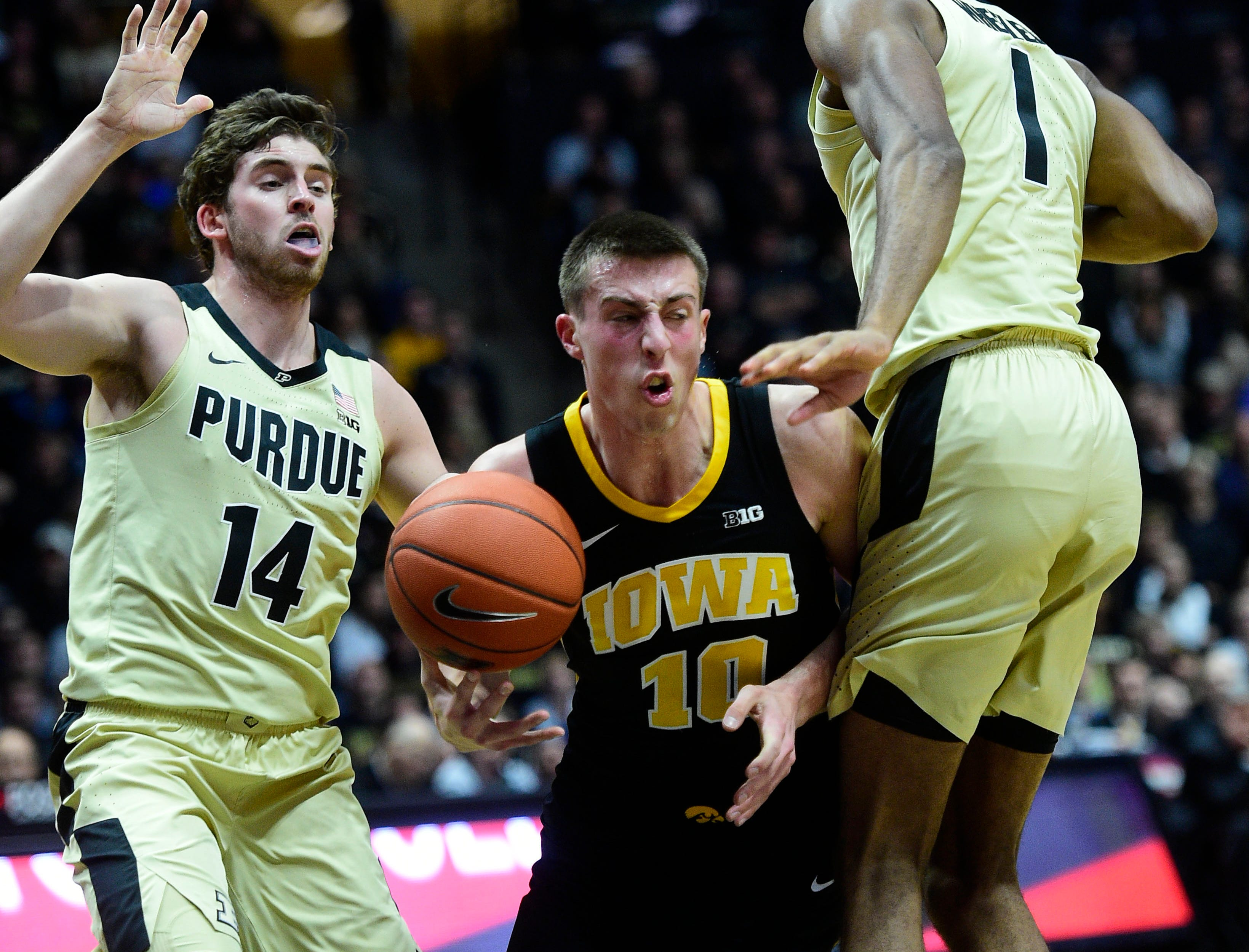 Jan 3, 2019; West Lafayette, IN, USA;  Iowa Hawkeyes guard Joe Weiskamp  (10) controls the ball between Purdue Boilermakers guard Ryan Cline (14) and forward Aaron Wheeler (1) in the first half at Mackey Arena. Mandatory Credit: Thomas J. Russo-USA TODAY Sports