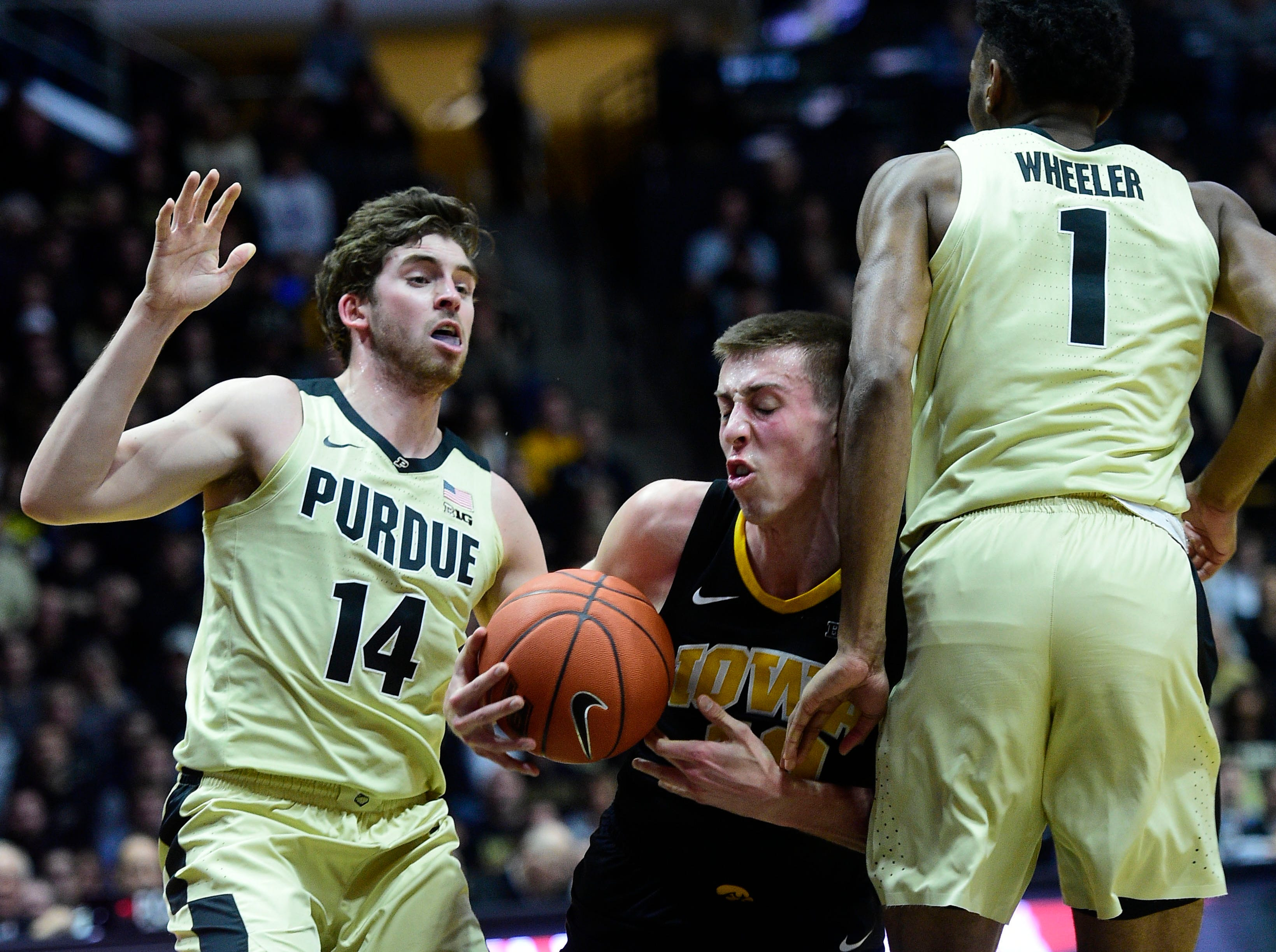 Jan 3, 2019; West Lafayette, IN, USA;  Iowa Hawkeyes guard Joe Weiskamp  (10) drives between Purdue Boilermakers guard Ryan Cline (14) and forward Aaron Wheeler (1) in the first half at Mackey Arena. Mandatory Credit: Thomas J. Russo-USA TODAY Sports