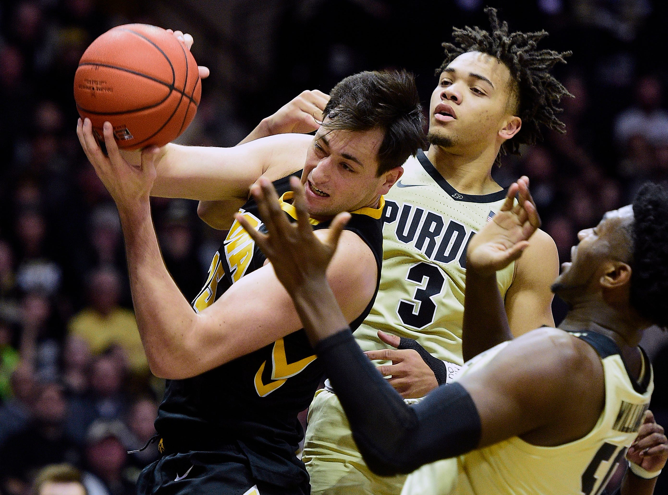 Jan 3, 2019; West Lafayette, IN, USA; Purdue Boilermakers   guard Carsen Edwards (3) and Purdue Boilermakers forward Trevon Williams (50) battle Iowa Hawkeyes forward Nicholas Baer (51) for the ball  in the second half at Mackey Arena. Mandatory Credit: Thomas J. Russo-USA TODAY Sports