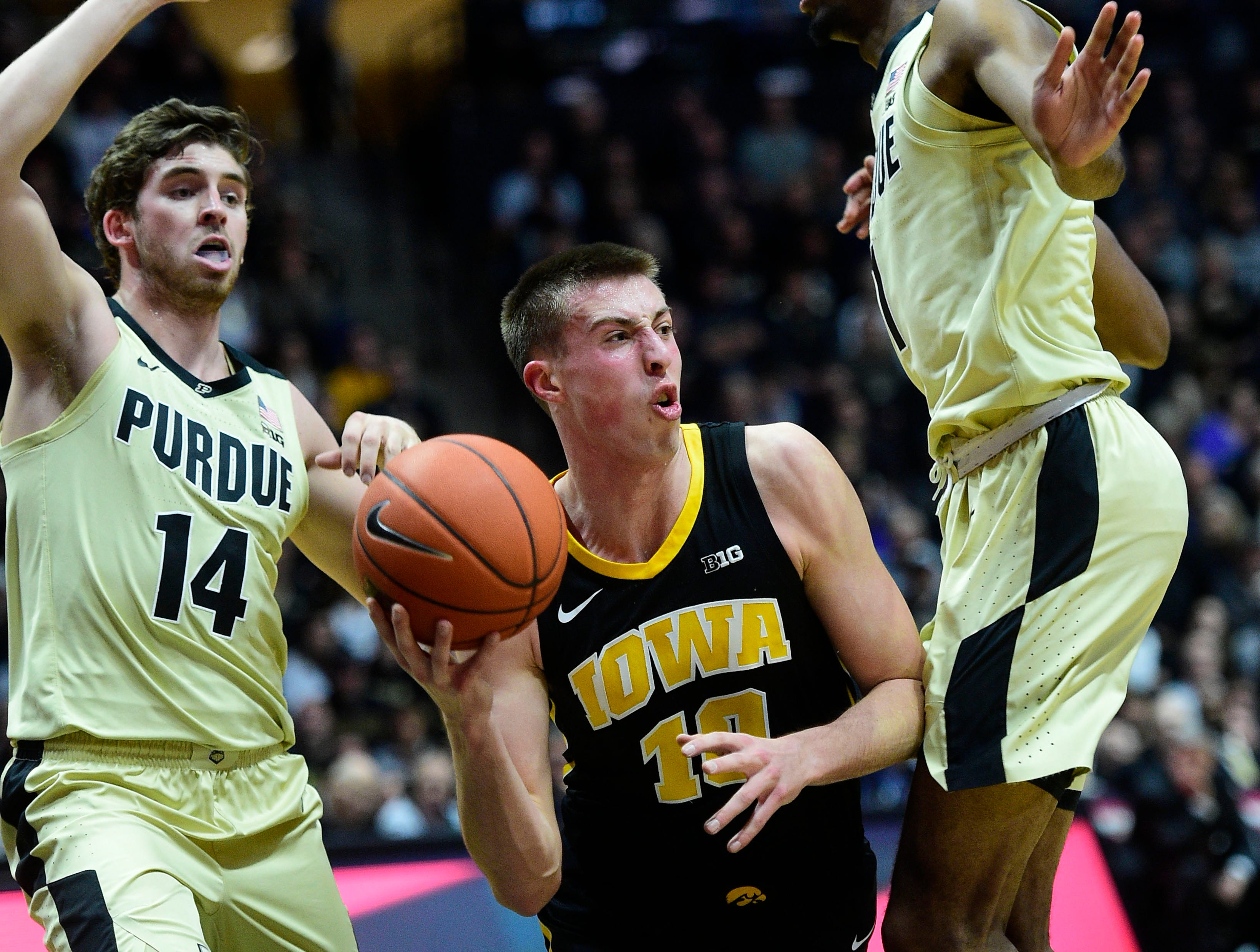 Jan 3, 2019; West Lafayette, IN, USA;  Iowa Hawkeyes guard Joe Weiskamp  (10) looks to pass the ball in Purdue Boilermakers guard Ryan Cline (14) and forward Aaron Wheeler (1) in the first half at Mackey Arena. Mandatory Credit: Thomas J. Russo-USA TODAY Sports
