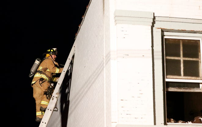 A firefighter climbs a ladder to check to the roof of a building Jan. 3, 2019, at 8516 Main St. in Rushville. A woman who was found in an upstairs apartment was flown to Ohio State University Wexner Medical Center for treatment, according the Bremen-Rushcreek Fire Chief William Duvall. The woman's name and condition weren't immediately available.