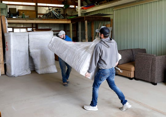 Josh Walters, left, and Bryce Walters carry new couches into the warehouse of Compassion Furniture Bank Friday, Jan. 4, 2019, in Stoutsville. The furniture was donated from Josh Walters' company J.W. Floors & Remodeling. The furniture bank provides furniture on a referral basis to people in need in Fairfield and Pickaway counties.
