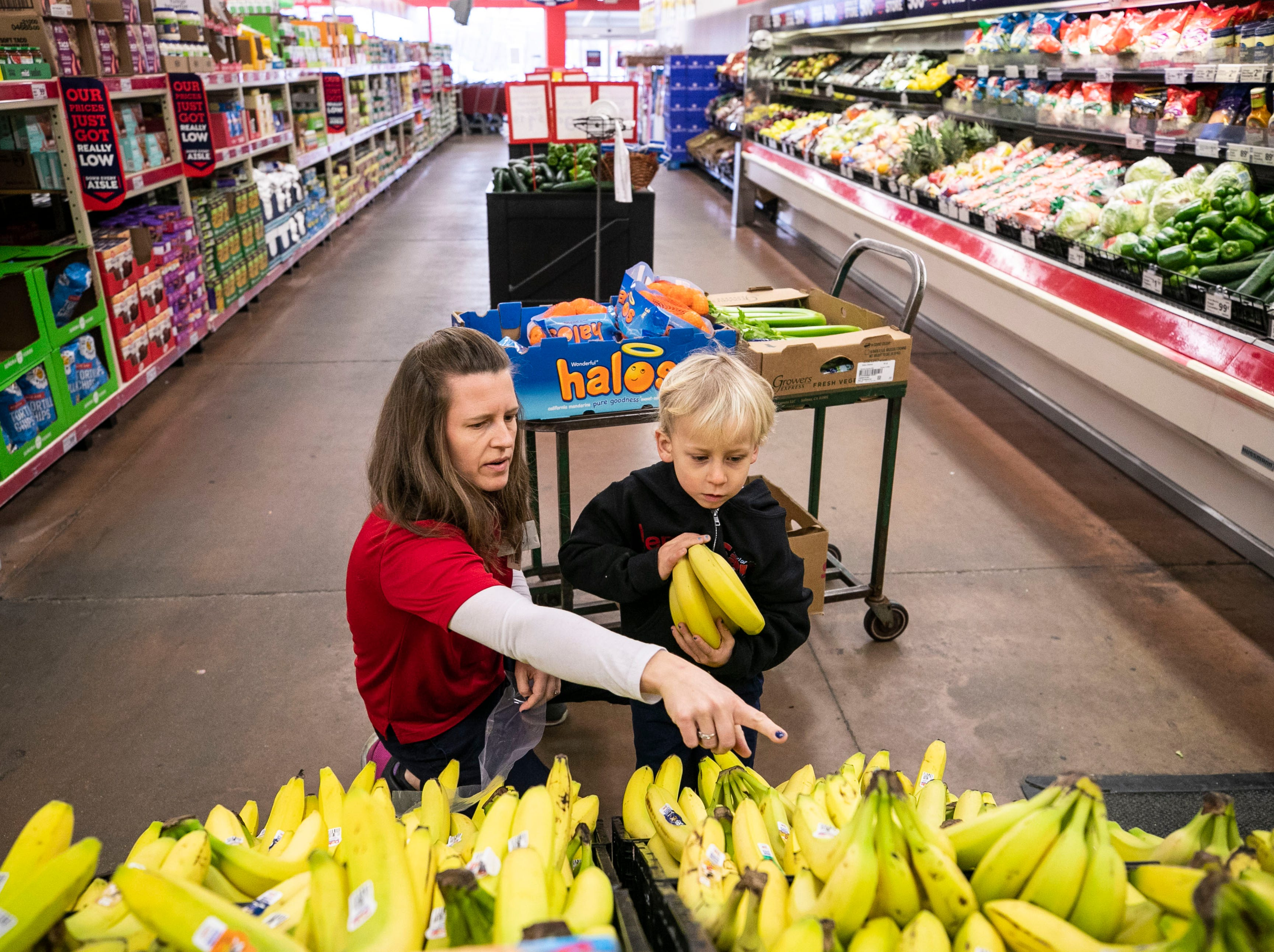 Jenny Kute and four-year-old son Henry put out fresh produce at the family's Save-A-Lot on Taylor Boulevard in the Hazelwood neighborhood of Louisville. Kute and husband Craig Oeswein had tailored the store to offer international foods for its customers as well as farm-to-store produce in the summer months. There is a farm behind the store's back lot that grows vegetables and the owners sell it at the store.