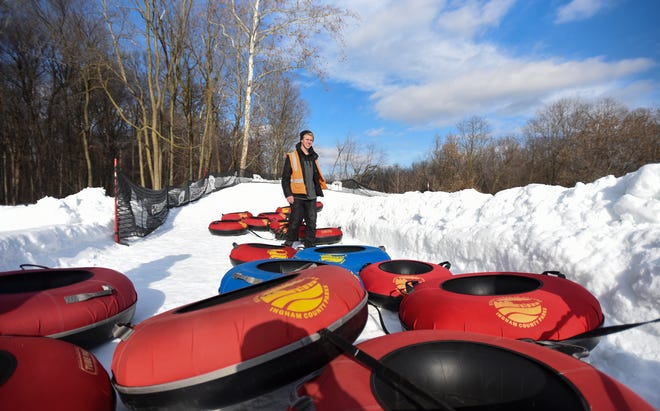 Josh Hossink of Ingham County Parks and Recreation hauls tubes to the storage area at Hawk Island County Park, near the base of the snow-tubing hill Thursday, Jan. 4, 2019.