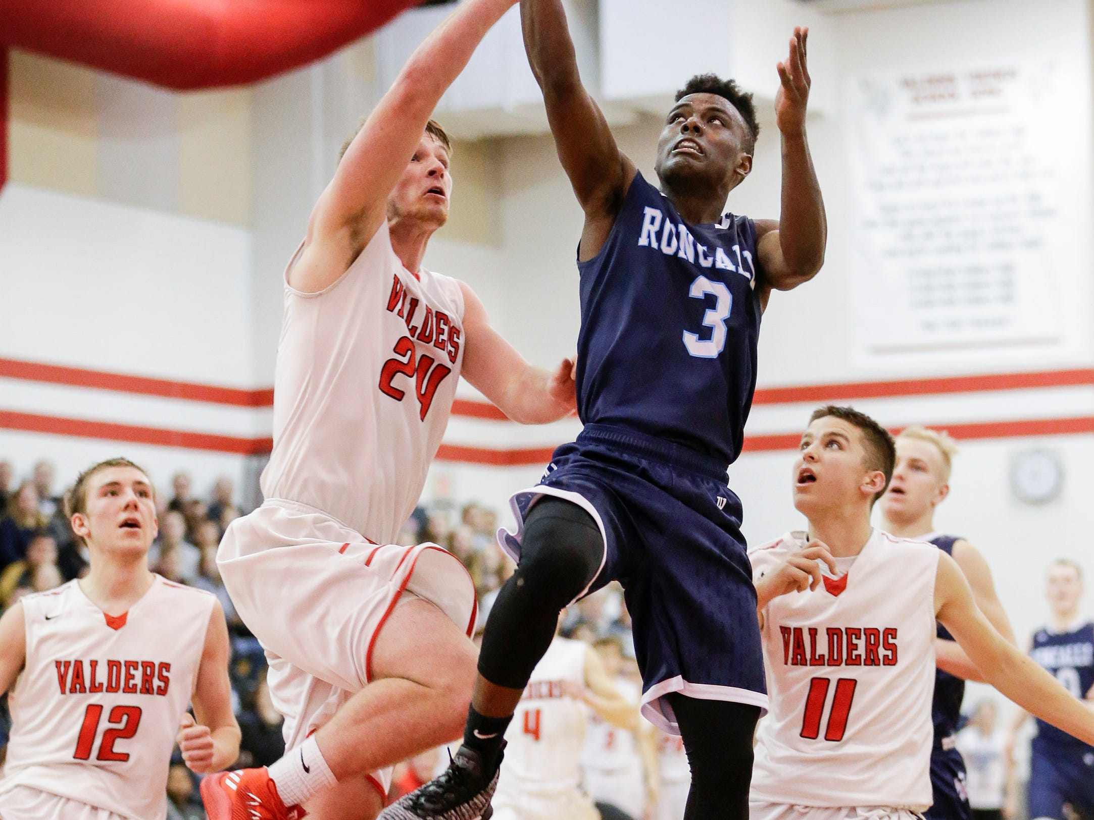 Roncalli's Chombi Lambert is fouled by Valders' Fletcher Dallas as he drives to the hoop during an Eastern Wisconsin Conference game at Valders High School Thursday, January 3, 2019, in Valders, Wis. Joshua Clark/USA TODAY NETWORK-Wisconsin