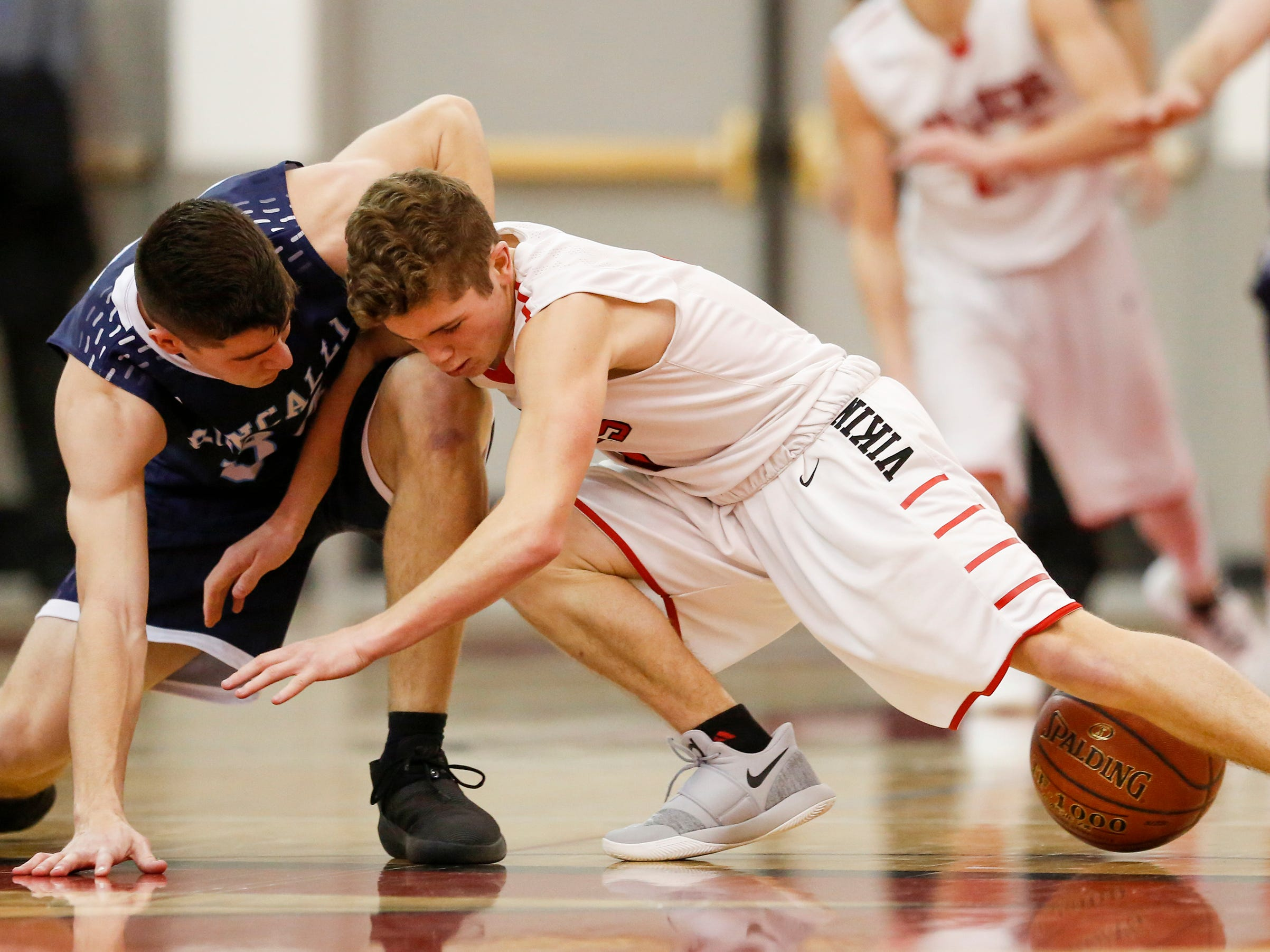 Roncalli's Ian Behringer (34) battles Valders' Nate Griepentrog (4) for a loose ball during an Eastern Wisconsin Conference game at Valders High School Thursday, January 3, 2019, in Valders, Wis. Joshua Clark/USA TODAY NETWORK-Wisconsin
