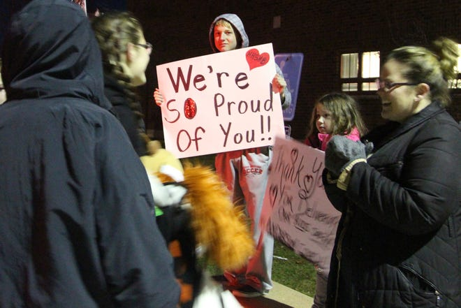 Family members lined the parking lot of Marion Harding High School with signs and balloons on Thursday as the award winning marching band returned home from a trip to Florida.