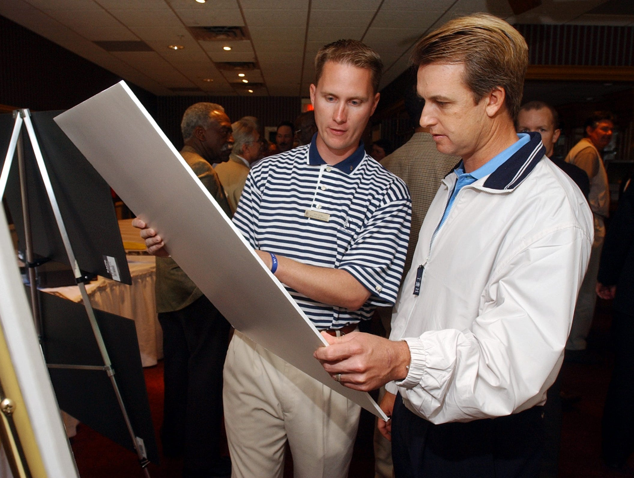 Wed, 14 Apr 04 (ddtoms1)  DIGITAL IMAGE by Dave Darnell.  Jon Goin (cq) (Left) and PGA tour player David Toms (cq) (Right) look over schematics showing changes to TPC Southwind during a luncheon at Germantown Country Club.  Goin is the head golf professional at Southwind and Toms is the defending champion of the FESJC.