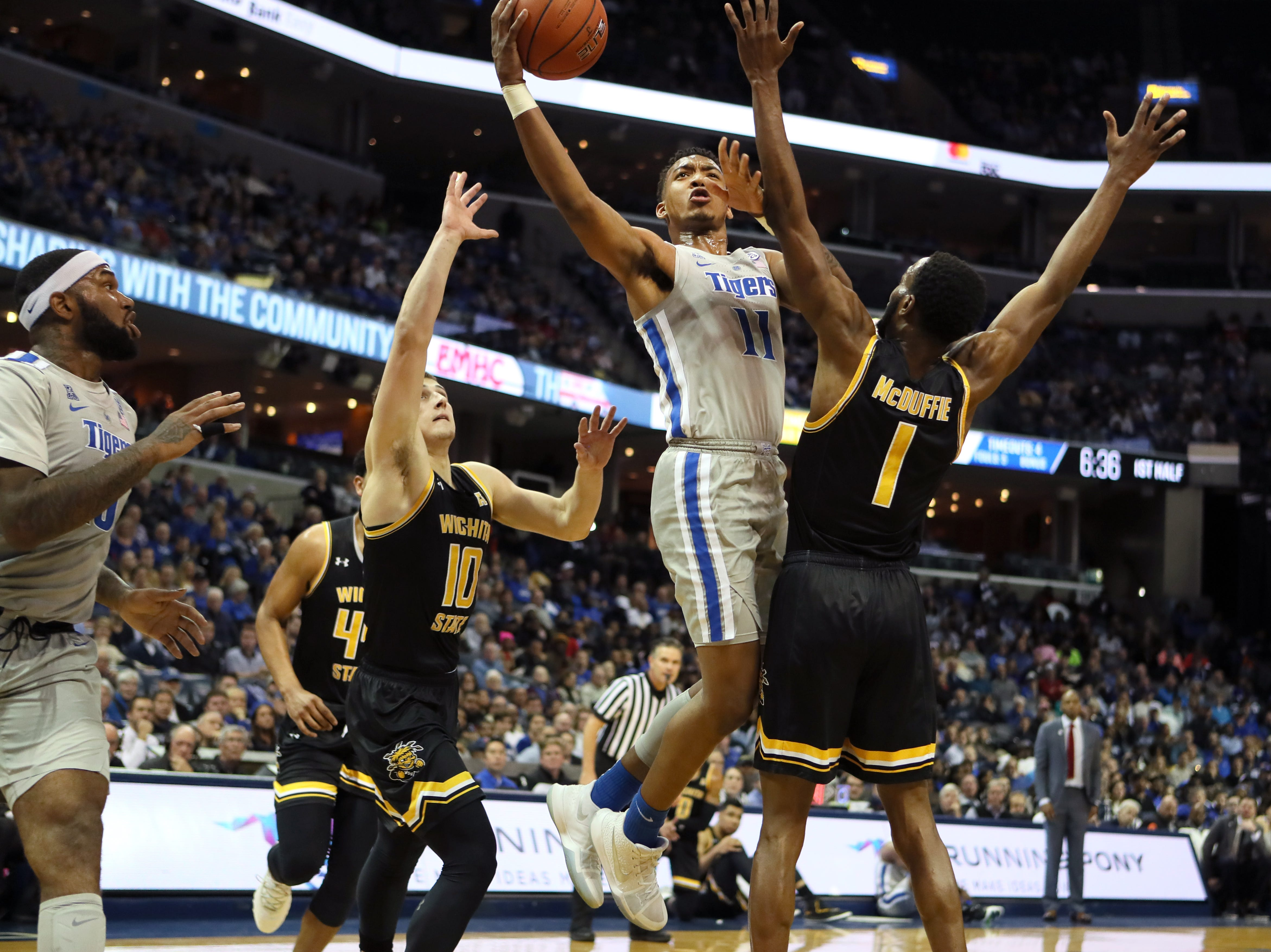 Memphis Tigers guard Antwann Jones shoots the ball over Wichita State Shockers guard Erik Stevenson, left, and Markis McDuffie during their game at the FedExForum on Thursday, Jan. 3, 2019.
