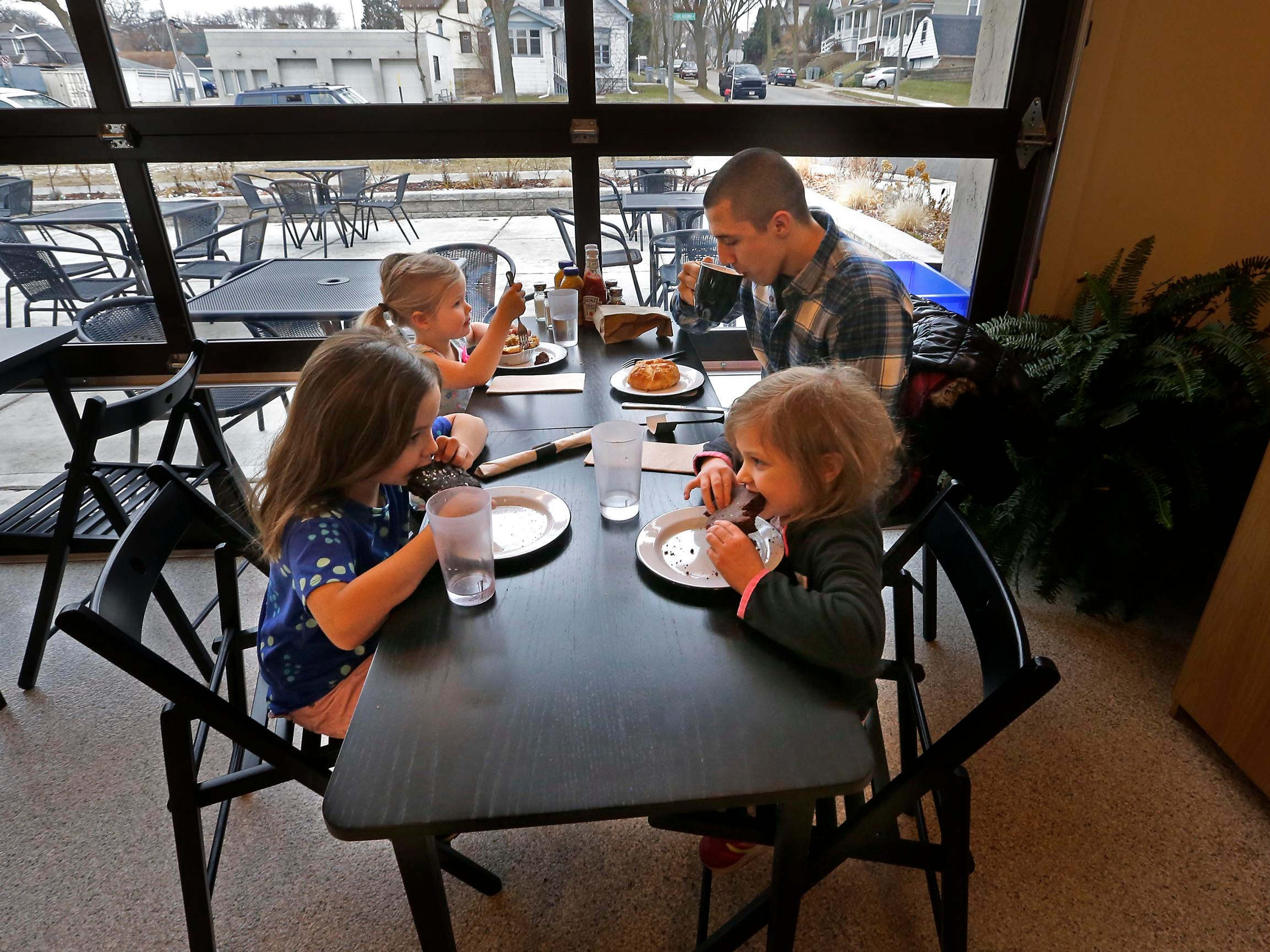 Ben Naus and his daughters Maisie, 3 (back);  Alane, 7 (left);  and Eleanor, (right) 5, from  Oak Creek enjoy an outing at  SmallPie in Bay View.