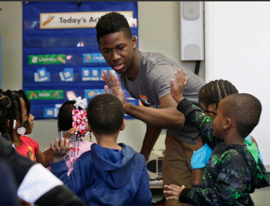 Isouma Shine high-fives students in a preschool class at Next Door Foundation in Milwaukee. Shine is taking part in the Leading Men Fellowship, a program aimed at improving early childhood literacy skills and exposing young men of color to careers in early childhood education.