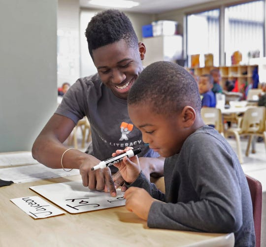Isouma Shine helps Jayceon Spicer write his name during sign-in time in a preschool classroom at Next Door Foundation.