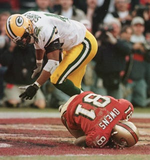 San Francisco 49ers receiver Terrell Owens hangs on for the game-winning touchdown despite a hard hit from Green Bay Packers defensive back Darren Sharper in the final seconds of the NFC wild card playoff game Jan. 3, 1999 at 3Comm Park in San Francisco.