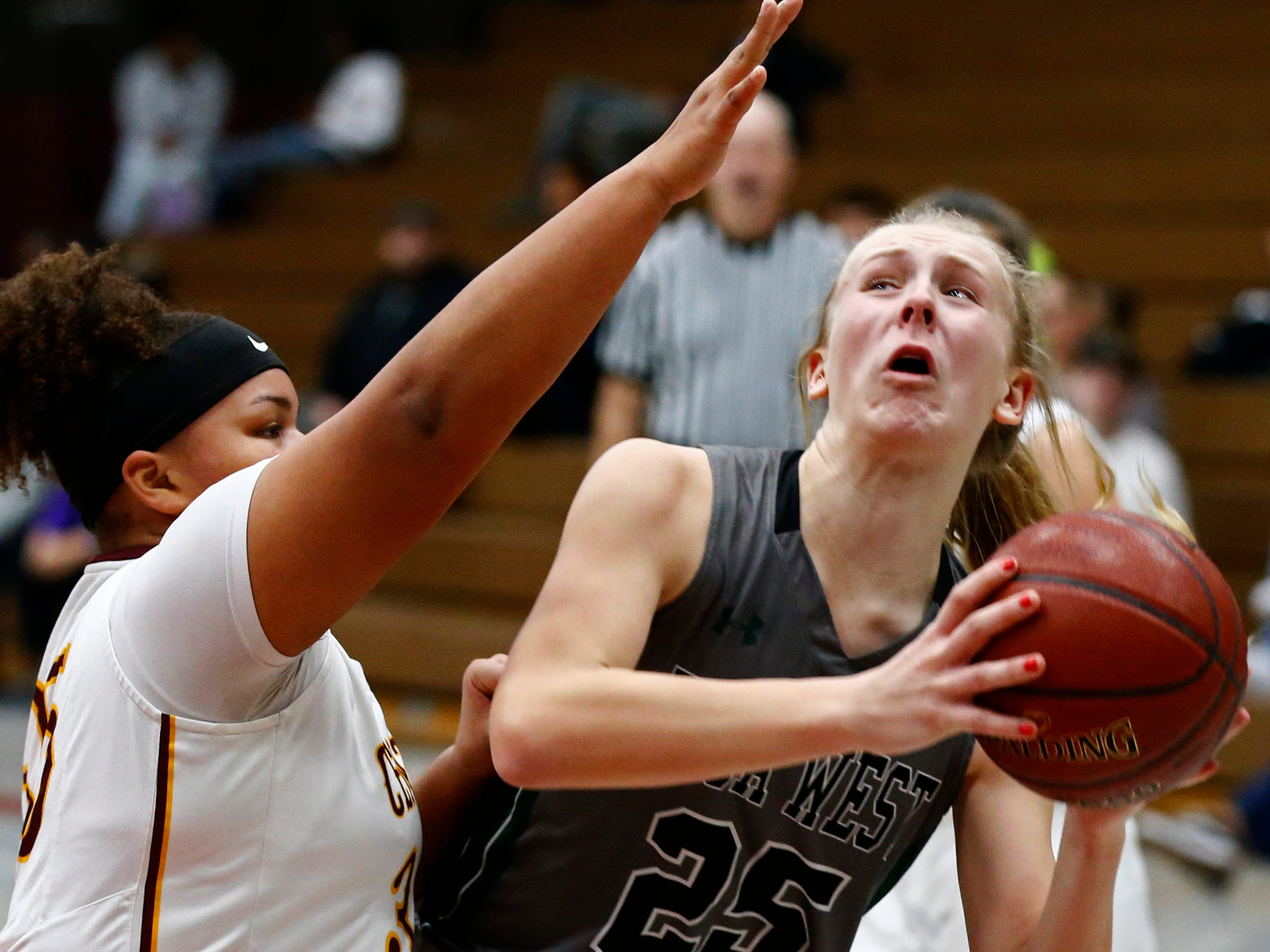 Wauwatosa West's Katie McCabe battles past West Allis Central's Rayne Conroy-Hubbard at Central on Jan. 3.