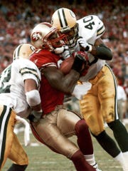San Francisco 49ers receiver Terrell Owens pulls in a 25-yard touchdown pass as Green Bay Packers' Pat Terrell (40) and Darren Sharper defend in the fourth quarter of the NFC wild card playoff game Jan. 3, 1999, in San Francisco. Owens' catch put the 49ers ahead 30-27 with three seconds left in the game.