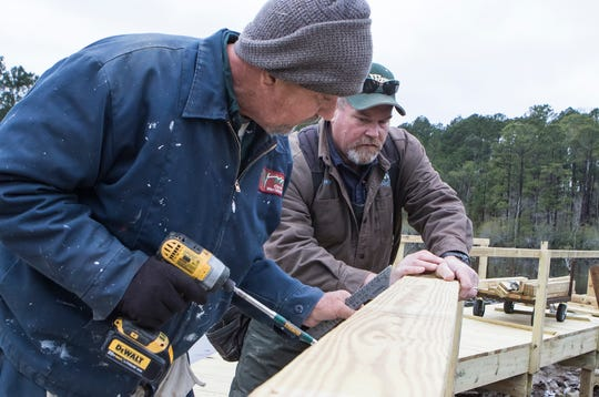 West Monroe city carpenters Billy Ferguson, left, and Donnie Watt install a new handrail on the new walkway bridge being constructed in Restoration Park in West Monroe, La. on Jan. 4. The original walkway needed to be replaced in the park due to it being unsafe.