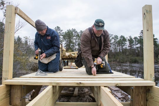 West Monroe city carpenters Billy Ferguson, left, and Donnie Watt drill down new walkway slats on the new walkway bridge being constructed in Restoration Park in West Monroe, La. on Jan. 4. The original walkway needed to be replaced in the park due to it being unsafe.