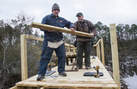 West Monroe city carpenter Donnie Watt, right, hands fellow carpenter Billy Ferguson a new walkway slat for the new walkway bridge being constructed in Restoration Park in West Monroe, La. on Jan. 4. The original walkway bridge needed to be replaced in the park due to it being unsafe.