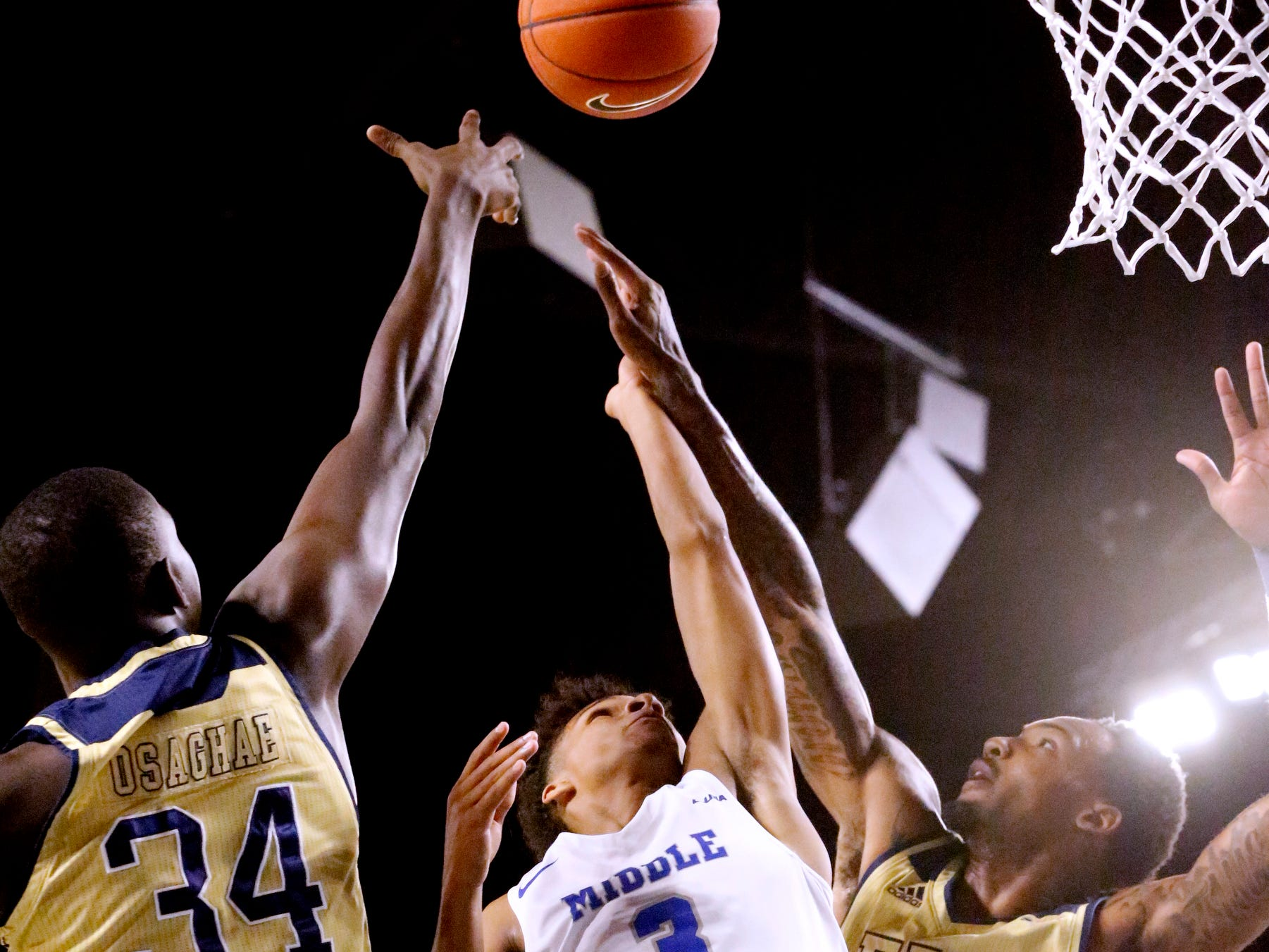 MTSU's guard Donovan Sims (3) goes up for a shot as he is guarded by FIU's forward Osasumwen Osaghae (34) and FIU's forward Devon Andrews (10) on Thursday Jan. 3, 2019, at MTSU.