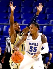 MTSU's guard Antonio Green (55) looks for a player to pass to as FIU's guard Marcus Burwell (11) guards him on Thursday Jan. 3, 2019, at MTSU.