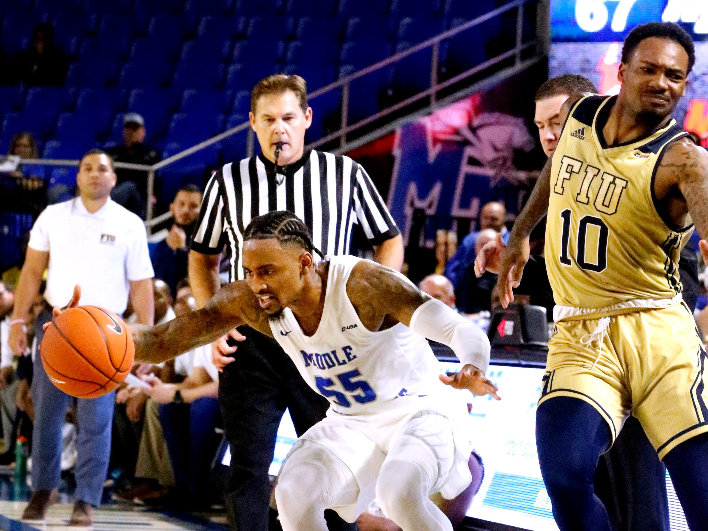 MTSU's guard Antonio Green (55) tries to stay in bounds as FIU's forward Devon Andrews (10) falls out of bounds on Thursday Jan. 3, 2019, at MTSU.
