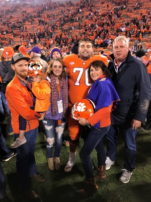 Clemson football player Seth Penner (70) stands on the field with his family following a game this season. From left: Penner's brother-in-law Ryan McLellan, niece Kinsley, sister Tori, mother Jeanne, and father Brian.