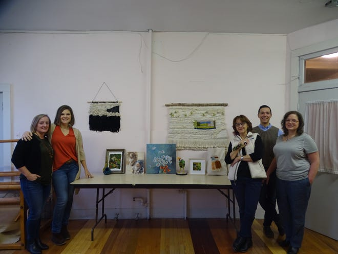 From left: Erin Eckenrode, Megan Henderson, Evelyn Frolking, Anton Sarossy-Christon, and Diana Andrews pose for a photo with their art in the Newark Cultural Arts Center in downtown Newark on Friday, Jan. 4, 2019.