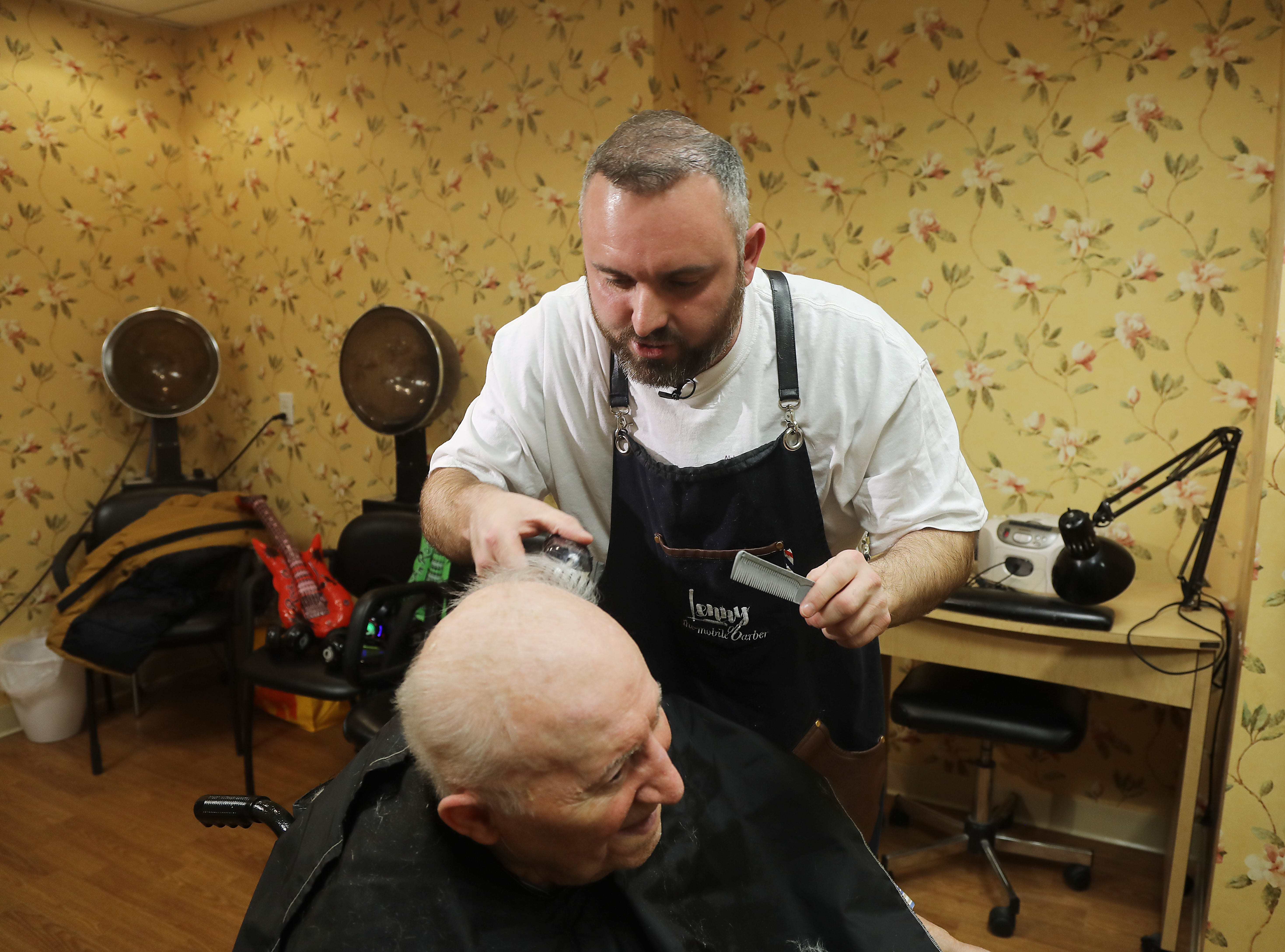 Lenny White, a barber from Northern Ireland, gives a complimentary haircut to Constantine Soukas 83 a resident of The Chelsea of Montville, an assisted living facility on January 3, 2019.