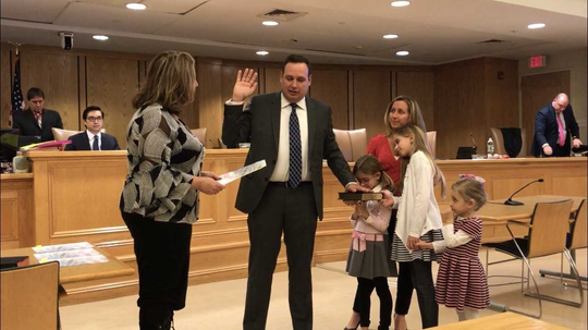 Assemblywoman Holly Schepisi swears in Robert Ferguson to his firm term as councilman at the Jan. 3 reorganization meeting while his family looks on.