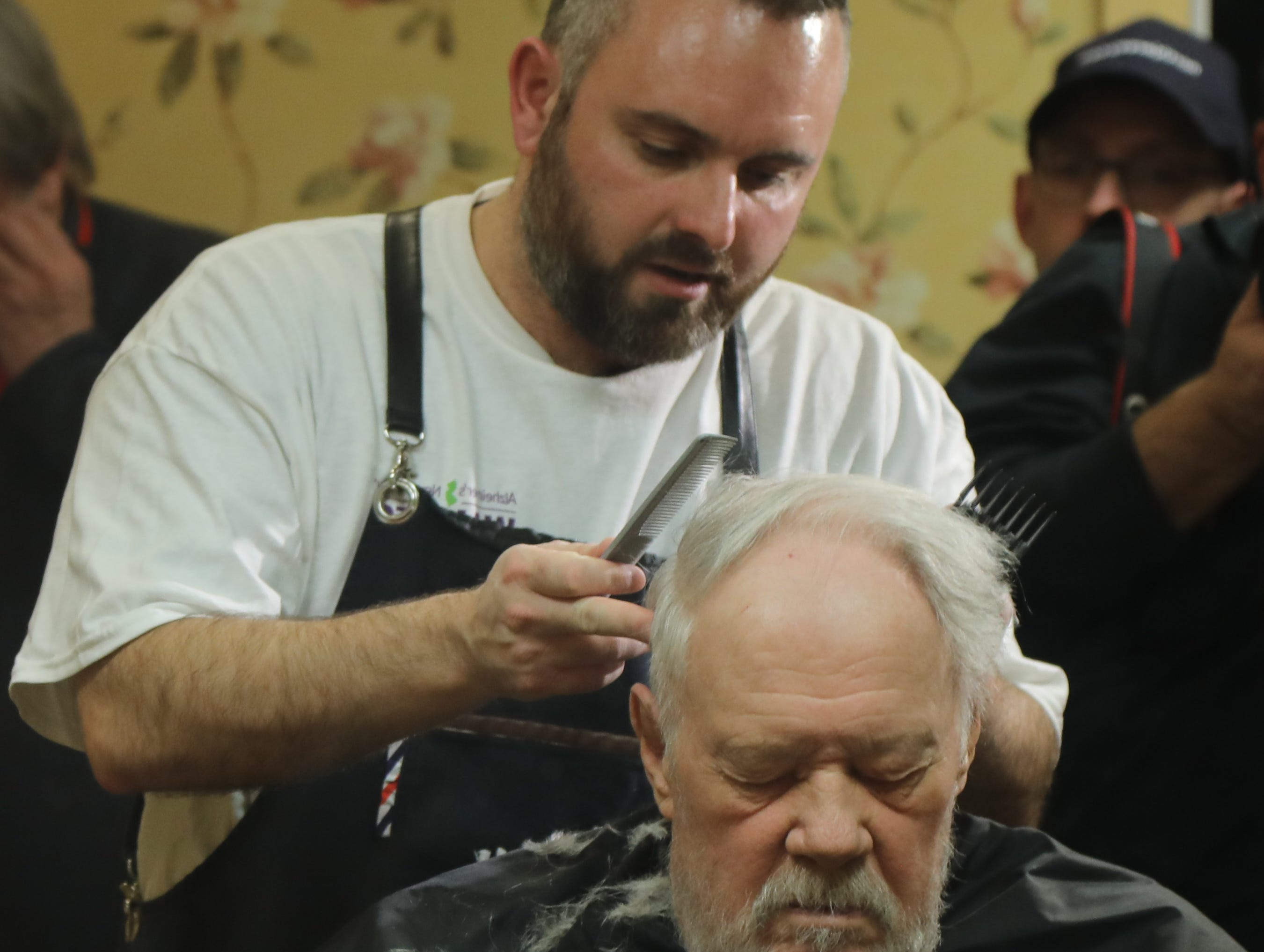 Lenny White, a barber from Northern Ireland, gives a complimentary haircut to Howard Smith 86.  Smith is a resident of The Chelsea of Montville, an assisted living facility in Montville Twp., NJ on January 3, 2019.