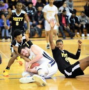 Schoolcraft's Alex Ismail dives to the floor and cradles the loose ball in front of two Mott players.