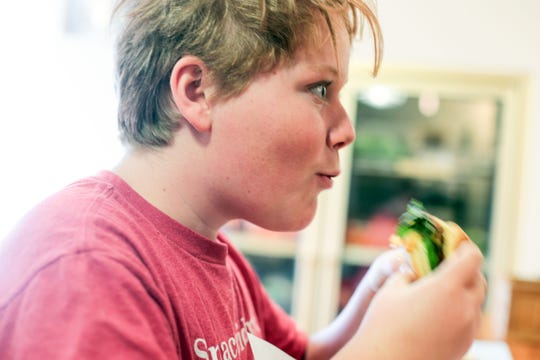 Aliyah Redding, 12,  enjoys his cheeseburger and fries at The  Sugarloaf Cafe on January 4, 2019 in Pinyon Pines
