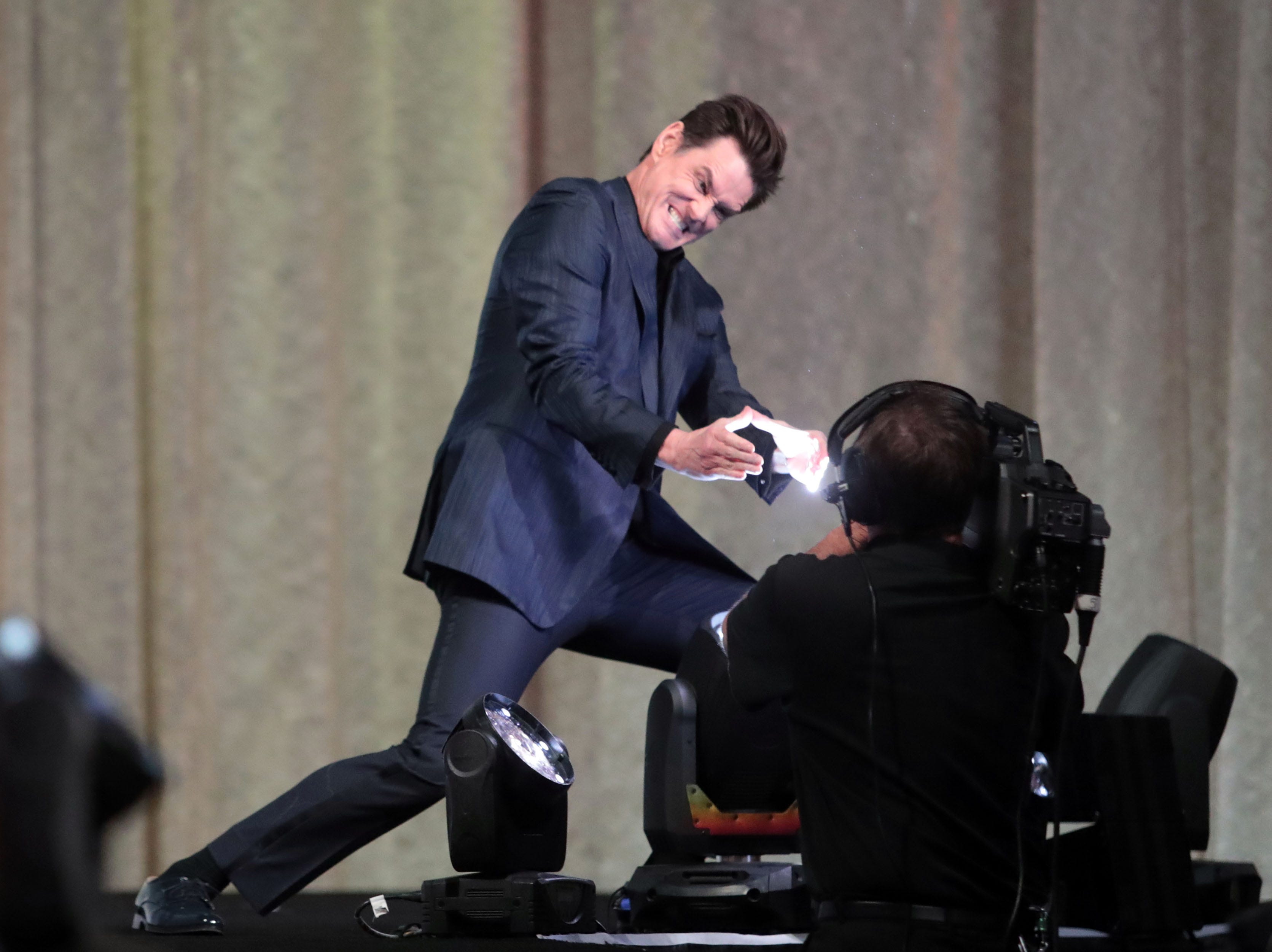 Jim Carrey fights a spotlight on Thursday, January 3, 2018 at the Palm Springs International Film Festival Gala in Palm Springs.