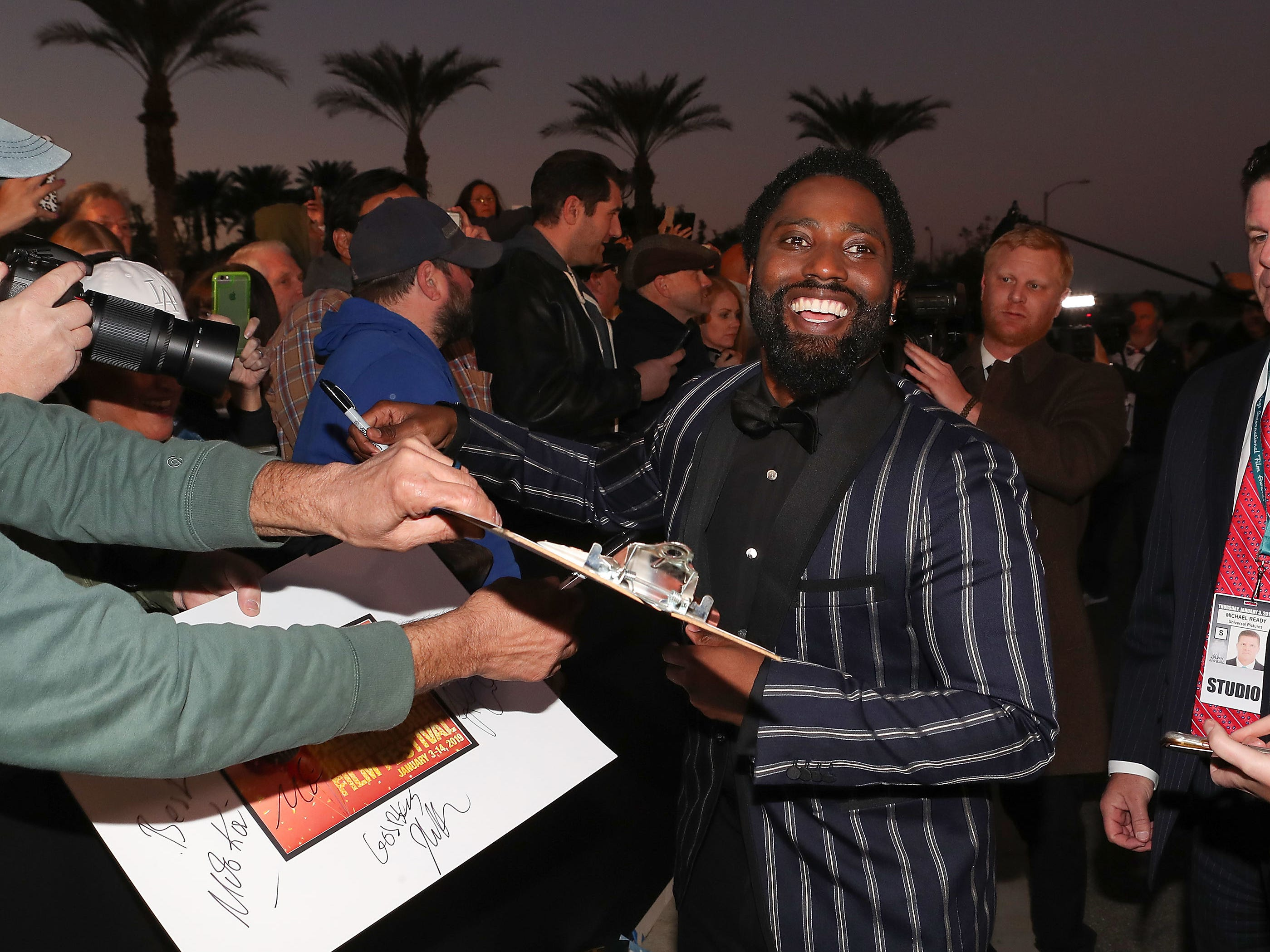 John David Washington signs autographs for fans at the Palm Springs International Film Festival Awards Gala, January 3, 2019.