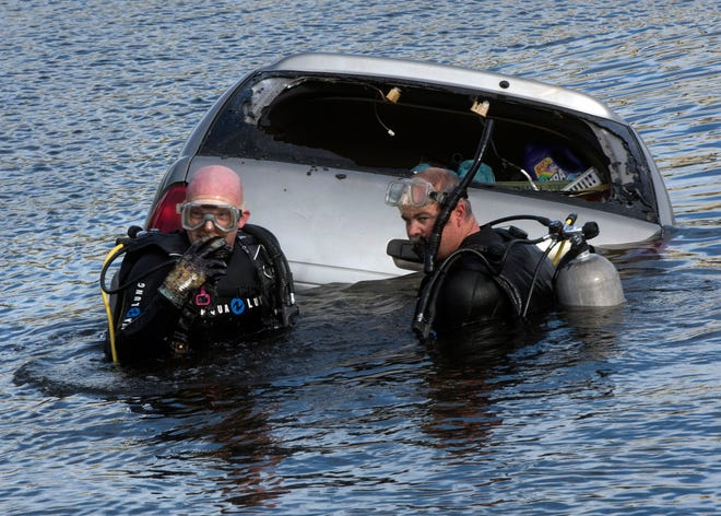 Emergency crews work Friday to remove a submerged vehicle from the Navy Point boat ramp.