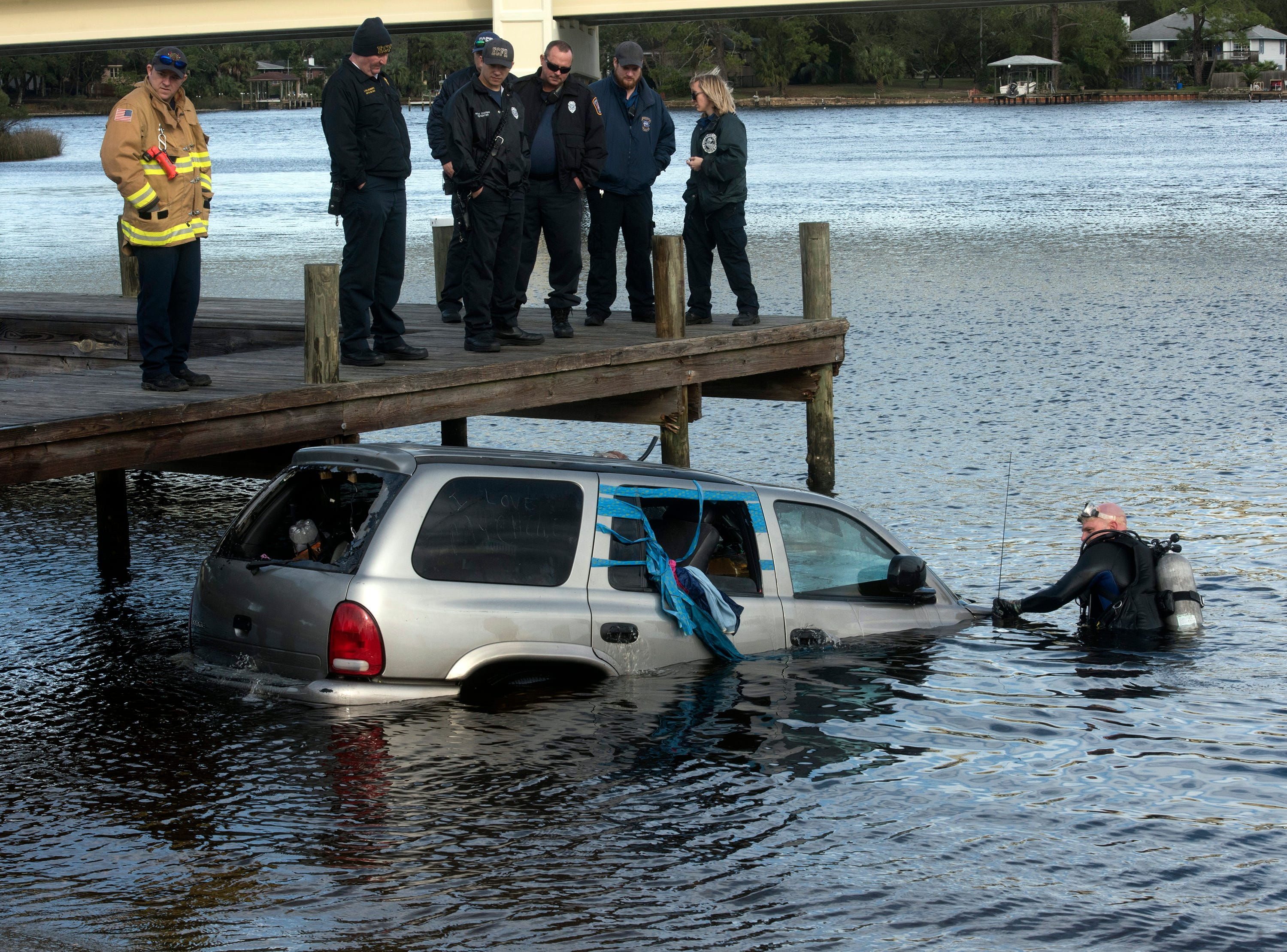 First responders from Escambia Fire Rescue, the Department of the Navy, Emergency Medical Services and Florida Patrol work to remove a submerged vehicle from the Navy Point boat Ramp on Friday, Jan. 4, 2019.