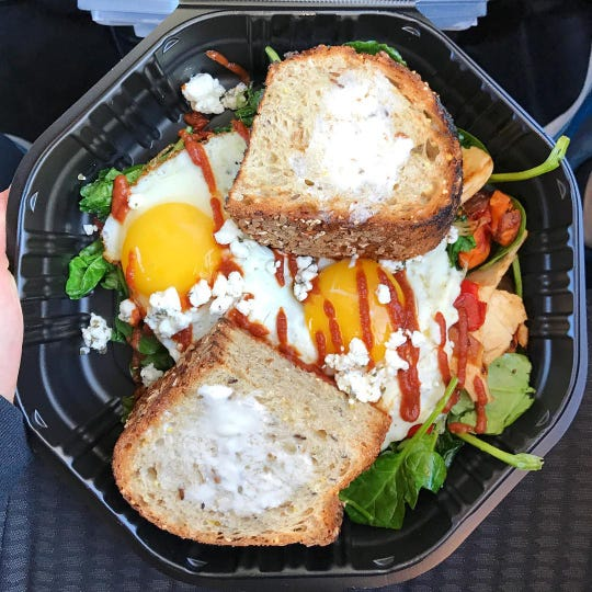 Wildflower's seasonal sweet potato and greens breakfast bowl is kale, spinach, red onions, red bell peppers, veracha, goat cheese and pepitas topped with sunny eggs. Artisan toast was added to this bowl.