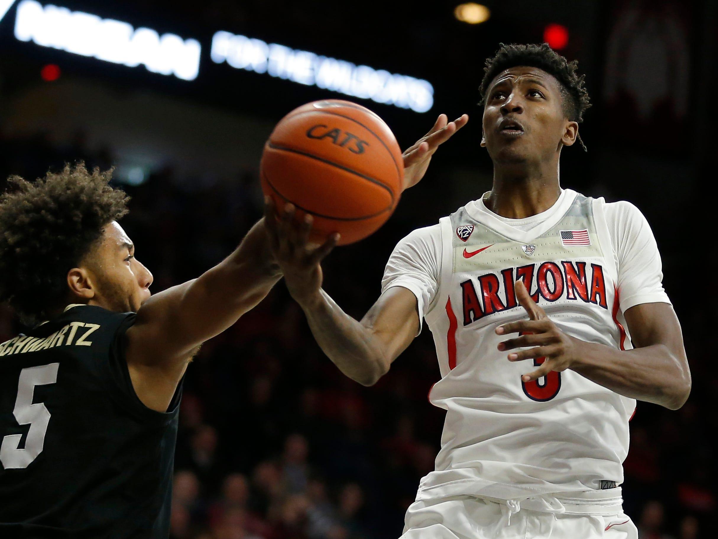 Arizona guard Dylan Smith drives past Colorado guard D'Shawn Schwartz (5) during the second half of an NCAA college basketball game Thursday, Jan. 3, 2019, in Tucson, Ariz. Arizona defeated Colorado 64-56. (AP Photo/Rick Scuteri)