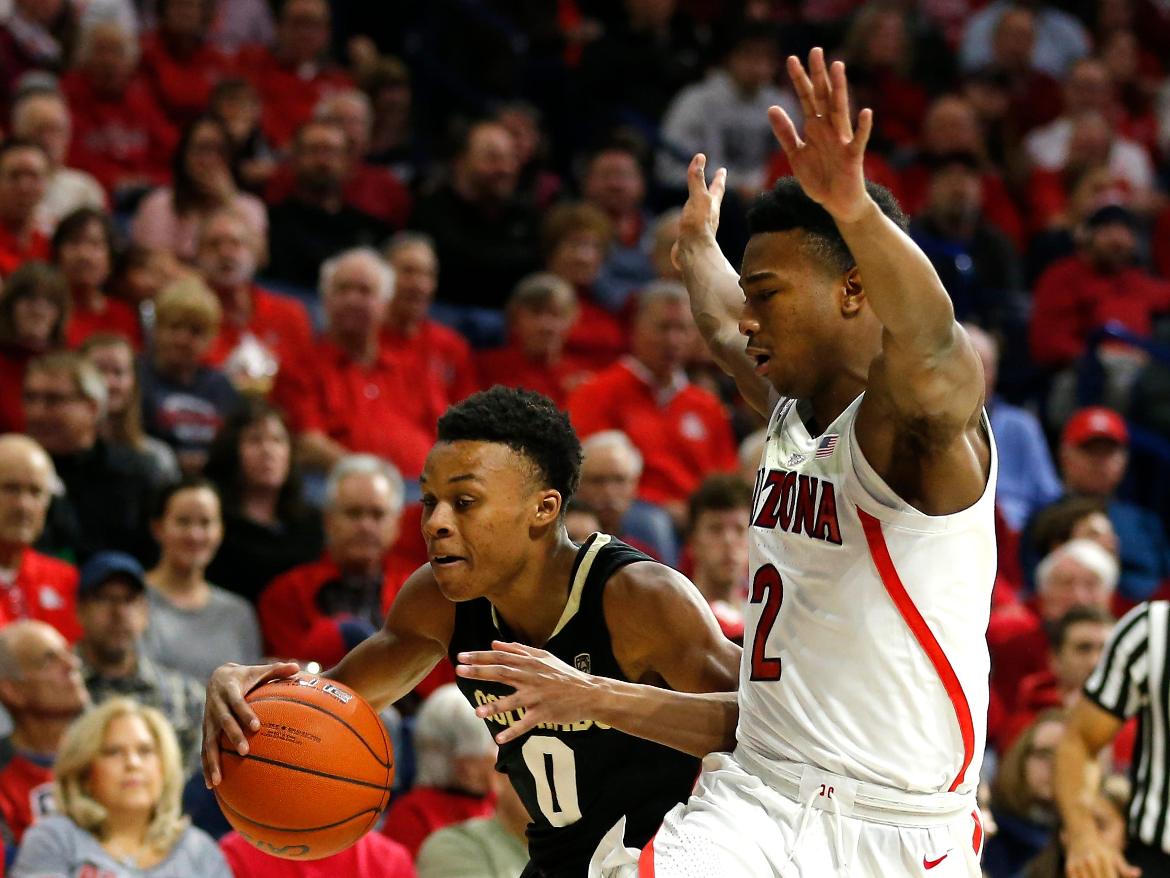 Colorado guard Shane Gatling (0) drives on Arizona guard Brandon Williams in the first half during an NCAA college basketball game, Thursday, Jan. 3, 2019, in Tucson, Ariz. (AP Photo/Rick Scuteri)