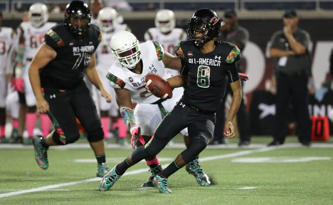 Team Ballaholics quarterback Jayden Daniels (8)  runs out of the pocket as Team Flash defense end Zach Pickens (26) pressures  during the second half at Camping World Stadium.