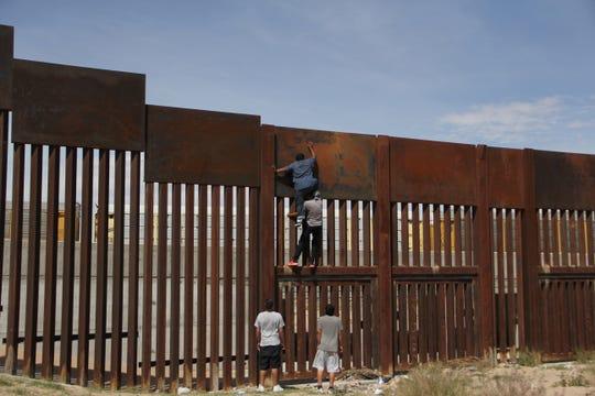 Unas personas intentan escalar la cerca fronteriza en Ciudad Juárez.
