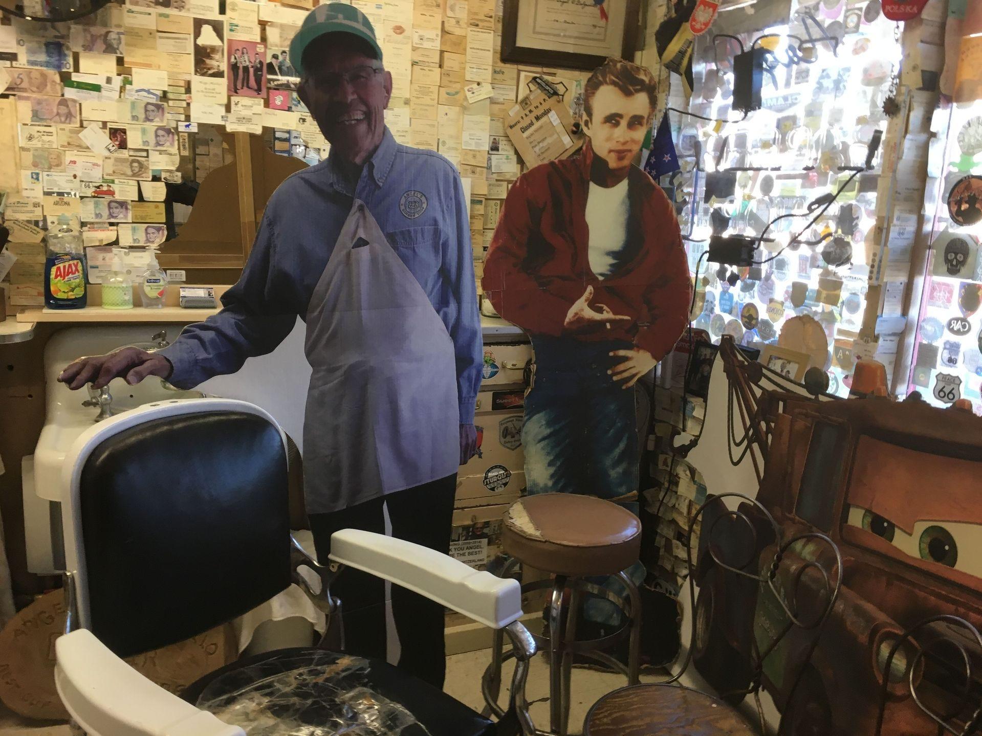 Cuando Ángel Delgadillo no está en su peluquería, su suplente de cartón saluda a los clientes.