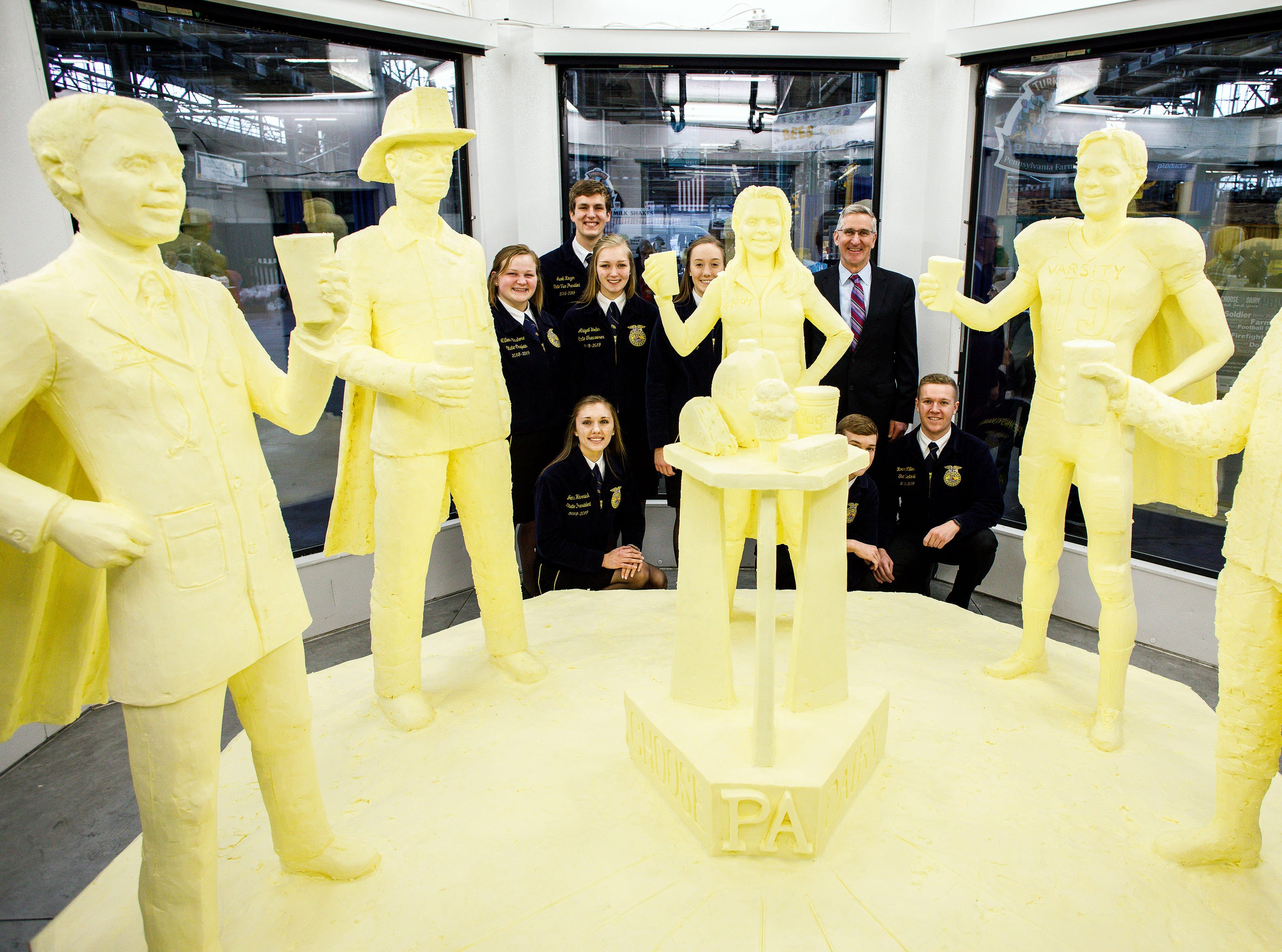 "Pennsylvania Secretary of Agriculture Russell Redding, top right, poses for a photo in the refrigerated case with state dairy princesses after the butter sculpture was revealed at the 103rd Pennsylvania Farm Show Thursday, Jan. 3, 2019, in Harrisburg, Pa. The sculpture, made from more than 1,000 pounds of butter, follows the theme of this year's Pennsylvania Dairy campaign, ""Find Your Power."" It depicts an athlete, soldier, doctor, firefighter and dairy farmer wearing superhero capes. (Dan Gleiter/The Patriot-News via AP)"