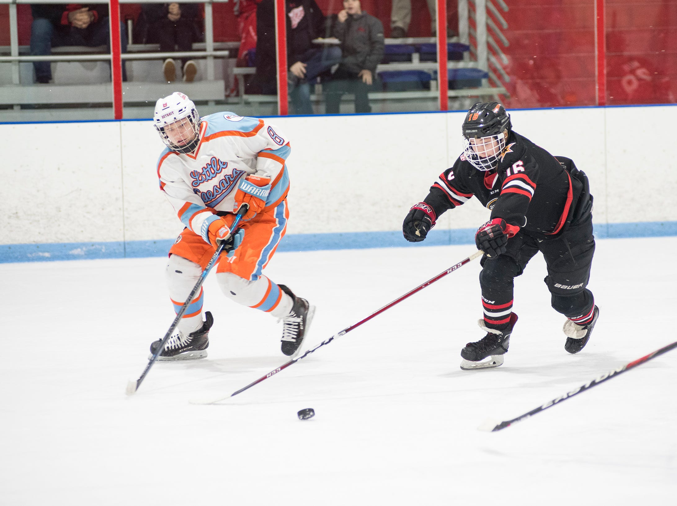 Indianapolis Jr Fuel defenseman Graham Wood (16) and Detroit Little Caesars forward Justin Varner chase the puck during their BAAA-A Silver Stick Finals match Friday, Jan. 4, 2019 at Glacier Pointe Ice Complex.