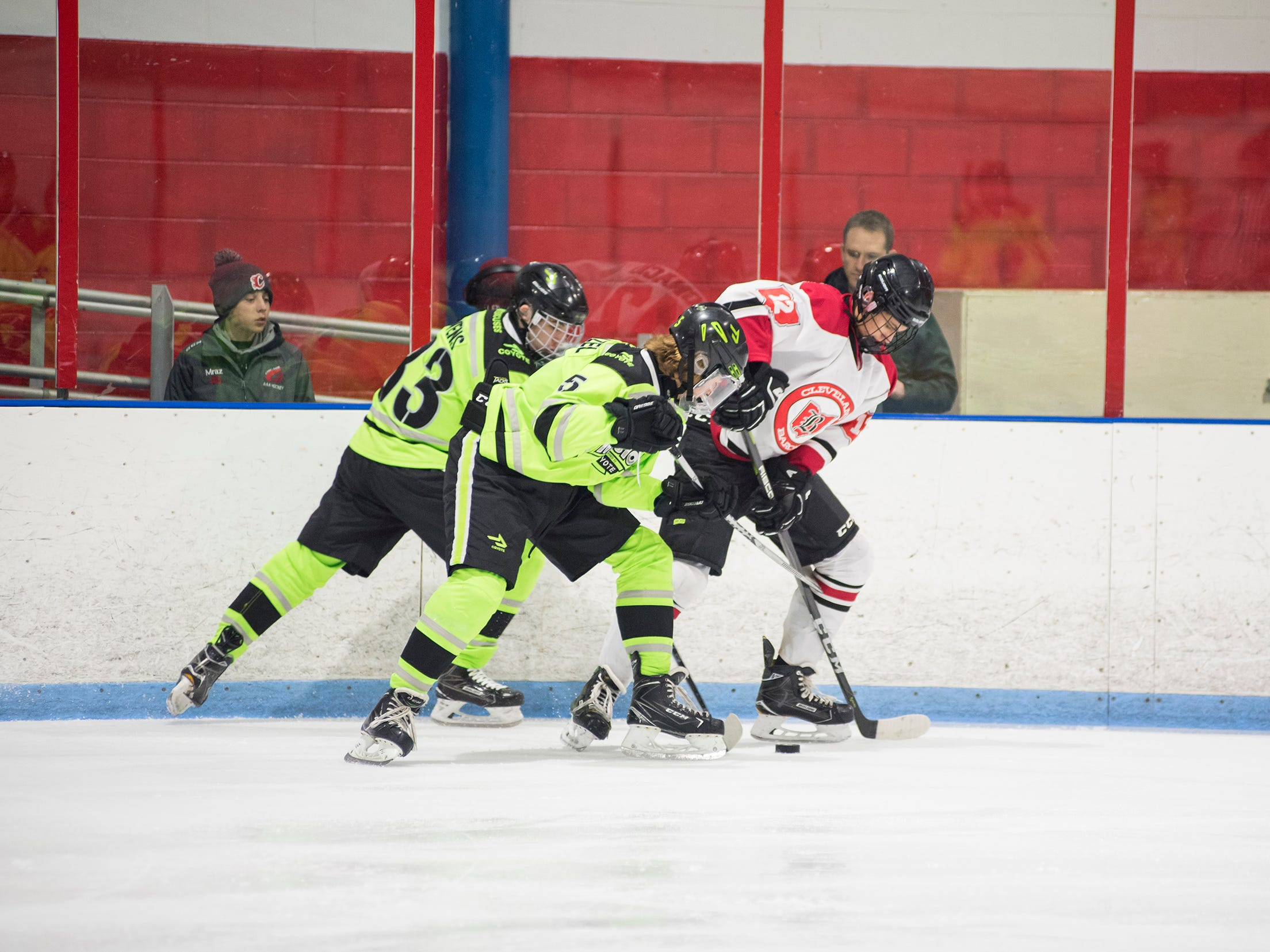 Chicago Mission defensman Zachary Frenzel (5), forward Raymond Owens (33) and Cleveland Barons Elite forward Alec Ignacio battle for the puck during their BAAA-C Silver Stick Finals match Friday, Jan. 4, 2019 at Glacier Pointe Ice Complex.