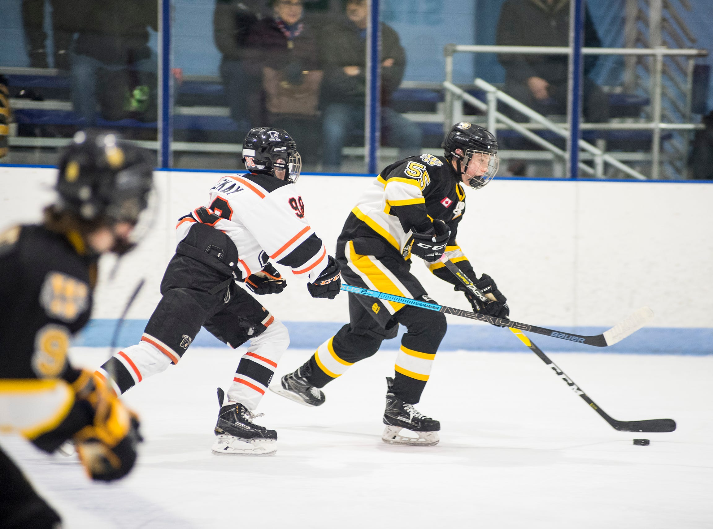 A Don Mills Flyers player reaches to steal the puck from Waterloo Wolves forward Hunter Nagge (55) during their BAAA-A Silver Stick Finals match Friday, Jan. 4, 2019 at Glacier Pointe Ice Complex.